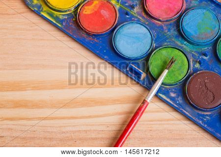 Dirty brush with paint on a wooden background