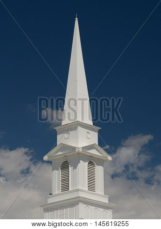 Christian Church steeple rising from clouds against blue sky