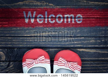 Welcome message and kid shoes on wooden floor