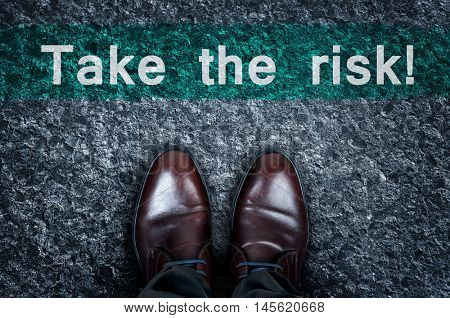 Take the risk message on asphalt and business shoes