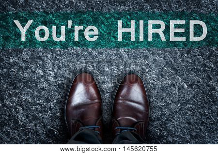 You're hired message on asphalt and business shoes
