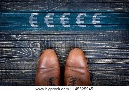 Euro sign message and business shoes on wooden floor