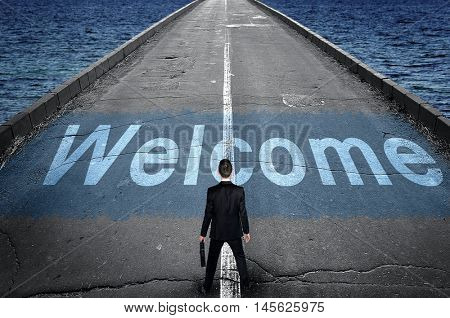 Welcome message on road and business man