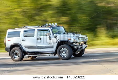Russia Irkutsk - 20 August 2015: Silver big Hummer car rides up the road at high speed. Frame transmitting movement