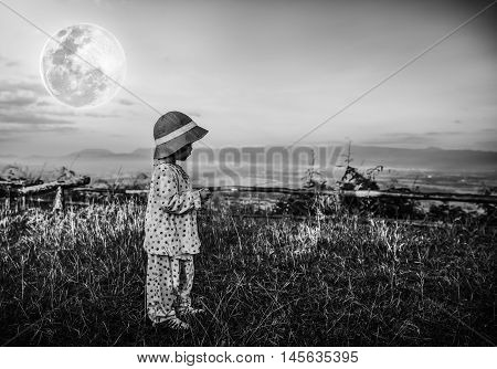 Asian child relaxing outdoors with bright full moon at night travel on vacation. Adorable girl in night sky under beautiful full moon. Black and white tone effect. The moon were NOT furnished by NASA.