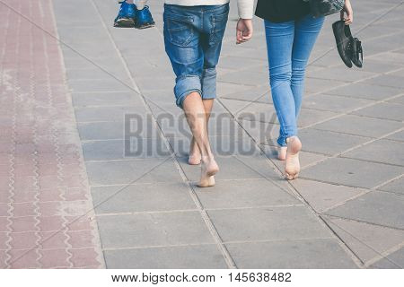 Happy couple walking barefoot on city waterfront on a sunny day