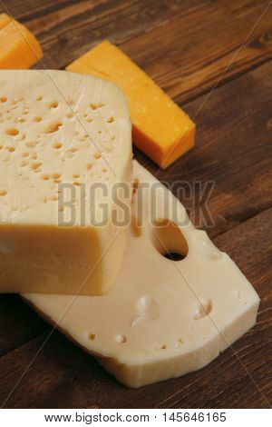 various types of fresh raw aged delicatessen cheese on wooden table cheddar edam swiss