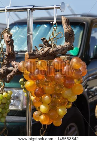 Stand with old vintage glass grape pendant at flea market