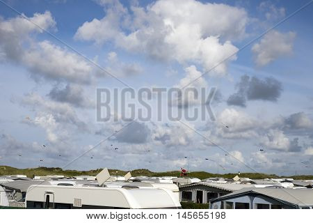 Danish campsite with caravans and campers all over. Kites in the air.