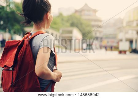 one young asian woman on city street