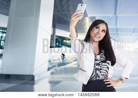 Asian business woman take selfie with her smartphone on the lobby success people concept