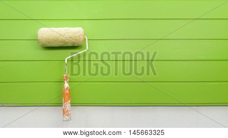 New paint roller isolated on wall green background.