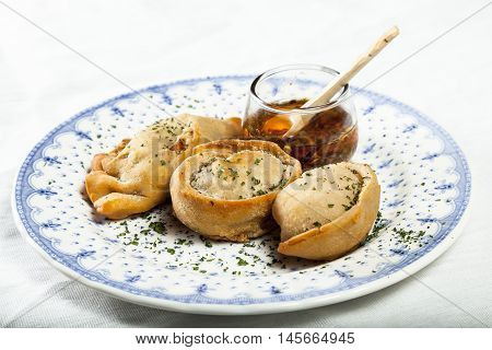 Three patties with spicy portion, on a decorated plate on blue