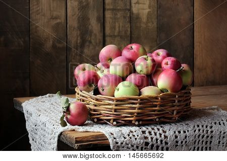 Apples in basket on a wooden table. Still life with apples in a rustic style.