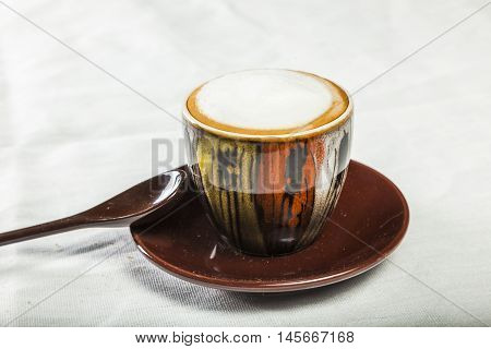 Cup with chocolate and spoom on white tablecloth