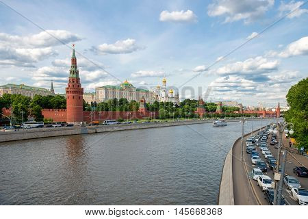 MOSCOW - JUNE 10 2016: the towers and walls of Kremlin. Kremlin Embankment. Pleasure boat floats on the river. The view from the big stone bridge.