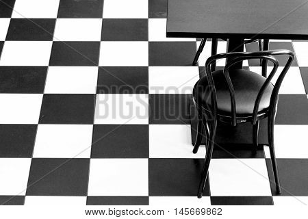 Black and white chess floor with black chair and table