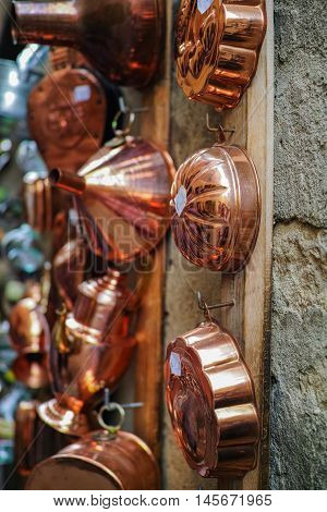 Copper kitchenware hanging on the wall in the shop Pienza italy
