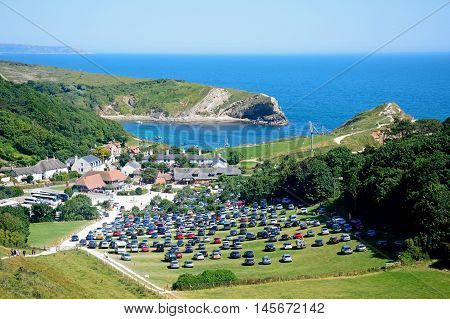 LULWORTH COVE, UNITED KINGDOM - JULY 19, 2016 - View looking down the hillside towards the cove and village with a car park in the foreground Lulworth Cove Dorset England UK Western Europe, July 19, 2016.