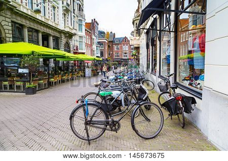 Hague, Netherlands - April 5, 2016: Row of bikes, cafe and dutch traditional houses on background in Den Haag, Holland