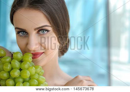 Close-up Portrait Of A Woman Who Is Holding Grapes