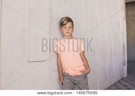 Trendy boy leaned on the wall and is confidently looking forward . He has cool hair . With one hand he put in his pocket . Children's fashion