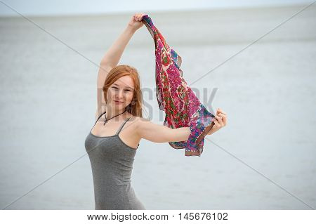 Red-haired woman holds up a colorful shawl