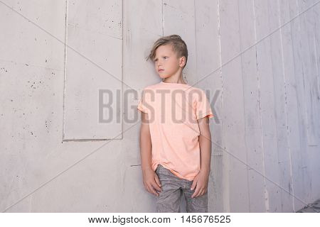 Stylish boy leaned on the wall and looking to the side . He's got great hair . Children's fashion
