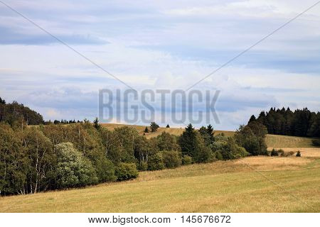 Dark clouds over the meadow. Change in the weather, the end of summer in Stolowe Mountains, Poland.