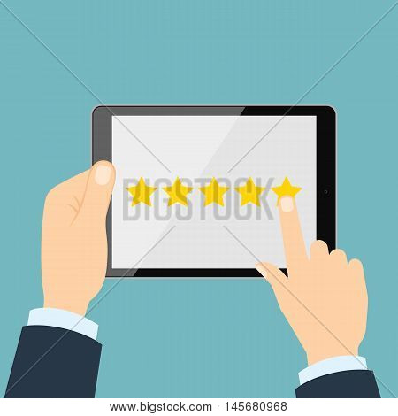 Ranking on tablet. Hands holding black tablet with yellow rank stars on screen. Man chooses stars for review and rating. Concept of voting and evaluation.