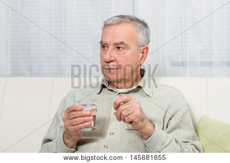 Disappointed senior man is sitting on the sofa and taking pills.