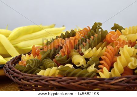 Three color pasta in a wicker bowl yellow bean pods on the glass plate
