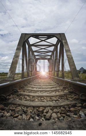 the length of railway with old steel bridge,filtered image,light effect added,selective focus,mean