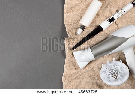 Hairstyling Tools (white Hairdryer, Hairspray, Spray, Cone Curling Wand) On Beige Towel. Top View