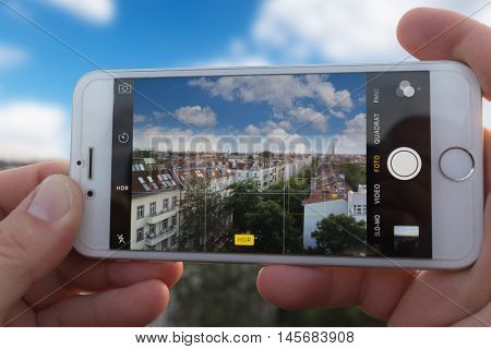 Berlin Germany - September 4 2016: Hands holding Iphone 6 using camera app to take a HDR picture of a city skyline.