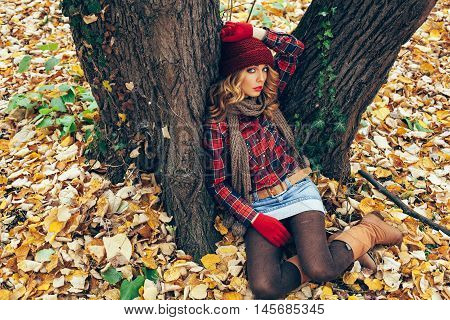 Women autumn fashion. Young woman sits leaning on a tree