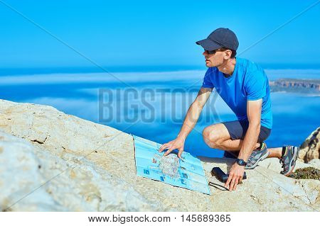 male traveler with backpack and map standing on the cliff against sea and blue sky at early morning