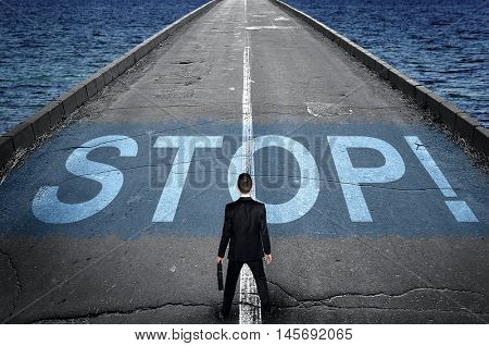 Stop message on road and business man