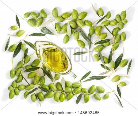 Top view of frame of green fresh olives with leaves and olive oil in a glass sauceboat isolated on white background.