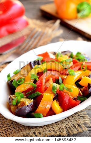 Vegetable stew on a plate. Diet stew with braised eggplant, red and orange peppers, garlic and green onion. Stewed vegetable mix. Hearty food. Wooden background. Closeup