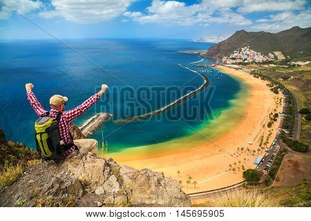 happy tourist man sitting on the edge of a cliff with outstanding overview of Playa de Las Teresitas Canary Islands Spain