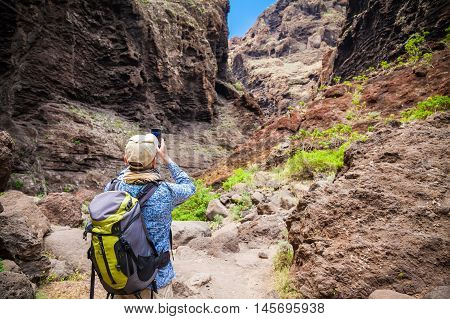 tourist man taking a photo of the beautiful famous canyon Masca in Tenerife Canary islands Spain