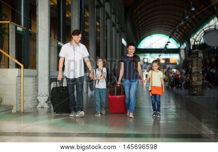 Young parents with a daughter and a son go through the waiting room at the station. Dad holds the hand of her son mother-daughter. The family is in a good mood. There are a lot of passengers.