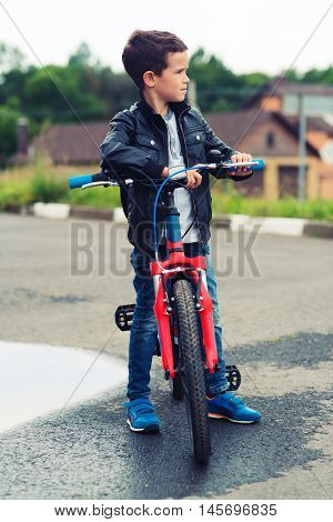 Cute boy riding bike in a city