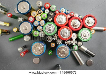 Selection of different batteries, top view on colorful commercial accumulators on gray background. Creative energy composition. Ecology concept