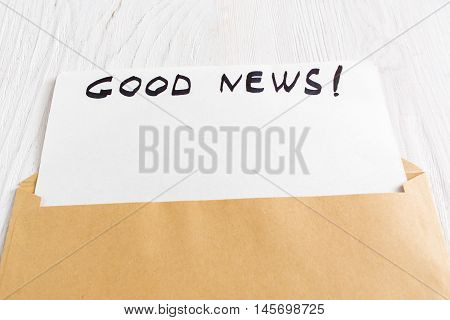 Blank greeting card in opened brown envelope with good news note. Greeting card with mockup on white paper