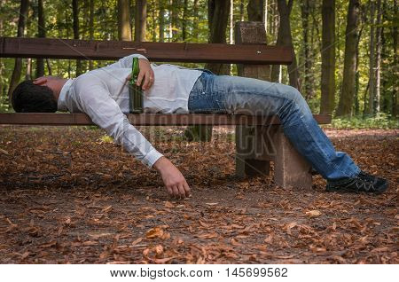 Depressed drunk man asleep outdoor on a park bench with beer bottles poster