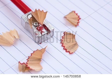 Color red art wooden pencil on a sharpener and shavings. Back to school concept