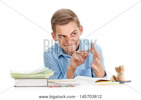Fun schoolboy with slingshot smiling near the desk with school supplies isolated on white cheerful childhood