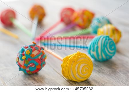 Cake pops of bright color. Candies with frosting. Find occasion for a party. Delicious mini cakes on sticks.